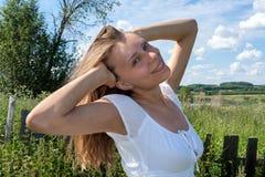 Jong glimlachend meisje in witte kleding met opgeheven wapens op achtergrond van het de zomerlandschap Royalty-vrije Stock Afbeeldingen