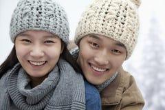 Jong Glimlachend Paar in de Sneeuw, die Camera bekijken royalty-vrije stock fotografie