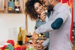 Jong glimlachend paar die groenten eten speels bij keuken royalty-vrije stock foto