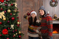 Jong glimlachend paar die Kerstboom in hun het leven r verfraaien Stock Afbeelding