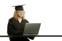 Jong graduatiemeisje dat computer met behulp van Stock Foto's