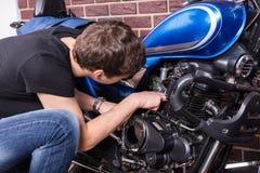 Jong Guy Fixing Some Parts van zijn Motor royalty-vrije stock afbeelding