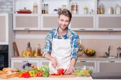 Jong het glimlachen mensen kokend diner in keuken Stock Afbeelding