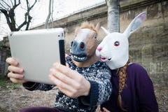 Jong hipster cuople paard en konijnmasker die tablet gebruiken Stock Foto's