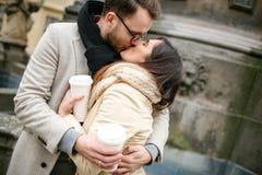 Jong hipsterpaar met koffie kussen, die in oude stad koesteren Royalty-vrije Stock Foto