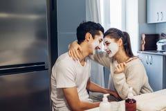 Jong houdend van paar die met gezichts thuis toegepaste maskers koesteren Huidbehandeling Rood nam toe royalty-vrije stock foto