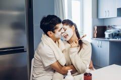 Jong houdend van paar die met gezichts thuis toegepaste maskers koesteren Huidbehandeling Rood nam toe stock afbeelding