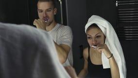 Jong houdend van paar die in spiegel kijken terwijl binnen het borstelen van tanden Dame die badhanddoek op haar hoofd dragen Slu stock videobeelden