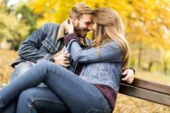 Jong houdend van paar op de bank in het de herfstpark Stock Foto