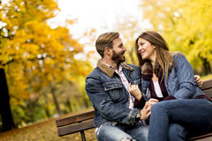 Jong houdend van paar op de bank in het de herfstpark Royalty-vrije Stock Afbeeldingen