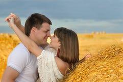 Jong houdend van paar op het gebied van hooiberg Stock Afbeelding