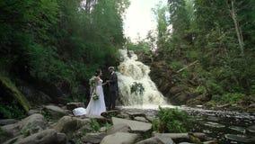 Jong huwelijkspaar bij ceremonie dichtbij waterval stock footage