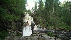 Jong huwelijkspaar die aan ceremonie dichtbij waterval lopen stock video
