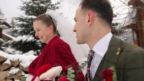 Jong huwelijkspaar die, hebbend de handen van de pretholding bij het dorp van de skitoevlucht met houten plattelandshuisjes dicht stock footage