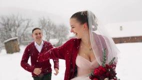 Jong huwelijkspaar die, hebbend de handen van de pretholding bij het dorp van de skitoevlucht met houten plattelandshuisjes dicht stock videobeelden