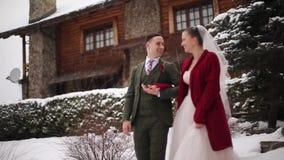 Jong huwelijkspaar die, het glimlachen en het spreken holdingshanden op treden bij het dorp van de skitoevlucht met houten platte stock videobeelden