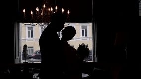 Jong huwelijkspaar die tegen een venster in silhouet dansen stock footage