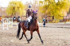 Jong jockeymeisje het berijden paard op de concurrentie Stock Afbeeldingen