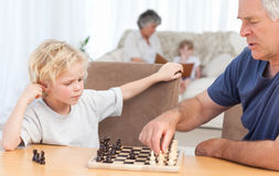 Jong jongen het spelen schaak met zijn grootvader Royalty-vrije Stock Afbeelding