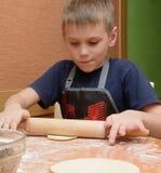 Jong jongens rollend deeg met een grote houten deegrol aangezien hij de cakes voorbereidt stock afbeeldingen