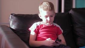 Jong jongens speelspel op smartphone in huis stock videobeelden