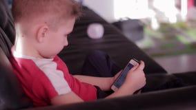 Jong jongens speelspel op smartphone in huis stock video