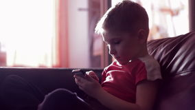 Jong jongens speelspel op smartphone in huis stock footage