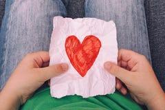 Jong jongensholding verfrommeld stuk van document met rode hartvorm Royalty-vrije Stock Afbeelding