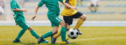 Jong Junior Football Match Spelers die en Voetbalbal in werking stellen schoppen royalty-vrije stock foto