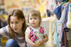 Jong Kaukasisch mamma met dochter bij de opslag van kinderen` s kleren Stock Foto's
