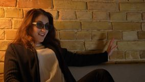 Jong Kaukasisch meisje dat met golvend haar in 3D glazen op TV met positief vermaak op comfortabele huisachtergrond let stock footage