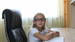 Jong Kaukasisch meisje die in glazen op stoel door lijst zitten Sluit binnen omhoog mening over mooi meisje in glazen wit Royalty-vrije Stock Afbeeldingen
