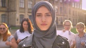 Jong Kaukasisch meisje die in hijab dicht met vertrouwen naast acteren feministische parade kijken stock video
