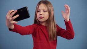 Jong Kaukasisch mooi meisje met lang haar die cheerfuly selfies op de telefoon nemen, die gezichten maken Het kijken op stock video