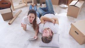 Jong Kaukasisch paar die op vloer in hun nieuwe vlakte in slowmotion liggen Concept samenhorigheid en huis stock footage