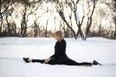 Jong Kaukasisch vrouwelijk blonde in beenkappen die oefeningszitting op een koord uitrekken bij openlucht in sneeuw bospasvorm en royalty-vrije stock foto