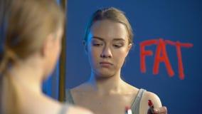 Jong Kaukasisch vrouwelijk het schrijven woord vet spiegelglas, tieneranorexiewanorde stock footage