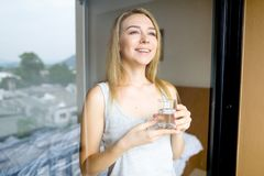 Jong Kaukasisch vrouwelijk persoon het drinken glas water in ochtend bij hotel royalty-vrije stock afbeeldingen