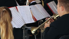 Jong kerelsspel op blaasinstrument in orkest stock videobeelden