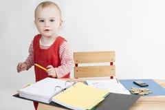 Jong kind bij het schrijven van bureau stock foto's