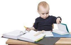 Jong kind bij het schrijven van bureau stock foto