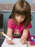 Jong kind dat bij haar bureau in klassenruimte werkt stock afbeelding