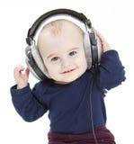 Jong kind dat met oortelefoons aan muziek luistert stock fotografie