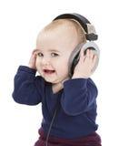 Jong kind dat met oortelefoons aan muziek luistert stock afbeeldingen