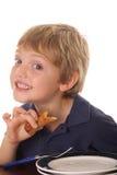 Jong kind dat over ontbijt glimlacht Stock Fotografie