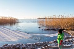 Jong kind die in de winterkleding een mooi koud zonnig toneel rustig de winterlandschap van ijs, water en riet tegen a bekijken stock afbeelding