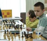 Jong kind die een beweging met een paard maken tijdens een schaaktoernooien op een school, met verscheidene andere concurrenten o Royalty-vrije Stock Fotografie