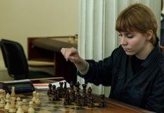 Jong kind die een beweging met een paard maken tijdens een schaaktoernooien op een school, met verscheidene andere concurrenten o Stock Foto
