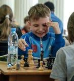 Jong kind die een beweging met een paard maken tijdens een schaaktoernooien op een school, met verscheidene andere concurrenten o Stock Afbeeldingen