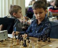 Jong kind die een beweging met een paard maken tijdens een schaaktoernooien op een school, met verscheidene andere concurrenten o Stock Afbeelding